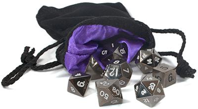 Photo of a black velvet dice bag spilling out a set of metal dice
